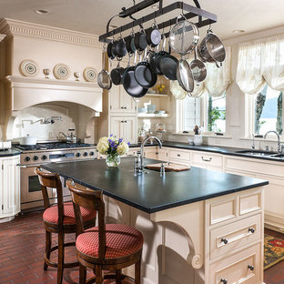 Inspiration for a mid-sized country l-shaped eat-in kitchen in Other with a double-bowl sink, recessed-panel cabinets, white cabinets, soapstone benchtops, white splashback, ceramic splashback, stainless steel appliances, brick floors and with island.