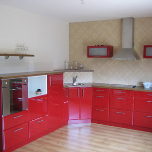 Inspiration for an eclectic kitchen in Other with flat-panel cabinets, stainless steel appliances, a drop-in sink, red cabinets and beige splashback.