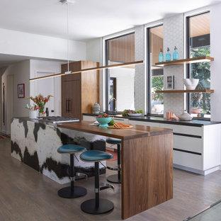 Idéer för att renovera ett mellanstort funkis svart svart kök, med släta luckor, vita skåp, träbänkskiva, mörkt trägolv, en köksö, en undermonterad diskho, vitt stänkskydd, fönster som stänkskydd, integrerade vitvaror och brunt golv