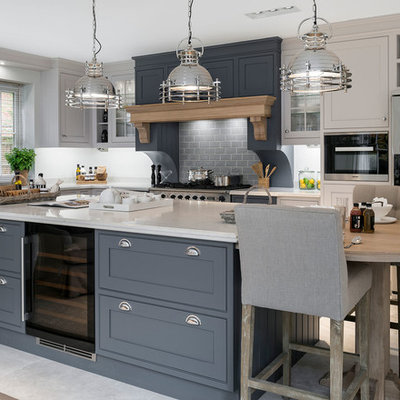 Mid-sized transitional l-shaped ceramic tile and beige floor kitchen photo in Hampshire with gray cabinets, solid surface countertops, stainless steel appliances, an island, shaker cabinets, gray backsplash and subway tile backsplash