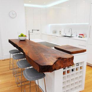 Diseño de cocina de galera, ecléctica, con fregadero de doble seno, armarios con paneles lisos, puertas de armario blancas, encimera de madera y encimeras blancas