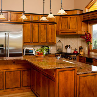 Inspiration for a mid-sized traditional l-shaped eat-in kitchen in Portland with a drop-in sink, beaded inset cabinets, medium wood cabinets, granite benchtops, beige splashback, terra-cotta splashback, stainless steel appliances, medium hardwood floors and with island.