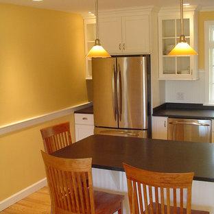ポートランド(メイン)の中サイズのコンテンポラリースタイルのおしゃれなキッチン (アンダーカウンターシンク、ガラス扉のキャビネット、白いキャビネット、白いキッチンパネル、木材のキッチンパネル、シルバーの調理設備の、無垢フローリング、マルチカラーの床) の写真