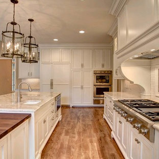 This is an example of a large traditional l-shaped open plan kitchen in Other with an undermount sink, beige cabinets, quartzite benchtops, white splashback, subway tile splashback, stainless steel appliances, with island, recessed-panel cabinets, medium hardwood floors and brown floor.