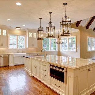 Cette photo montre une grand cuisine ouverte romantique avec un évier de ferme, des portes de placard beiges, un plan de travail en quartz, une crédence blanche, une crédence en carrelage métro, un électroménager en acier inoxydable et un îlot central.