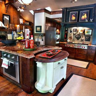 Aménagement d'une grand cuisine américaine montagne en L avec un évier de ferme, un placard avec porte à panneau encastré, des portes de placard en bois sombre, un plan de travail en granite, un électroménager en acier inoxydable, un sol en bois foncé, un îlot central, un sol marron et un plan de travail rouge.
