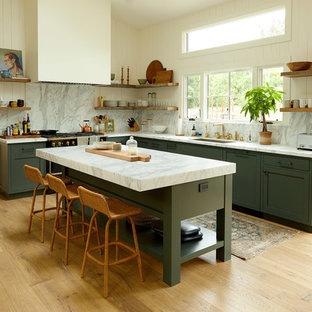 Inspiration for a country l-shaped eat-in kitchen in Santa Barbara with an undermount sink, shaker cabinets, green cabinets, white splashback, stone slab splashback, black appliances, medium hardwood floors, with island and brown floor.