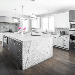 This is an example of a large contemporary l-shaped separate kitchen in New York with with island, a drop-in sink, flat-panel cabinets, white cabinets, marble benchtops, grey splashback, stainless steel appliances and plywood floors.