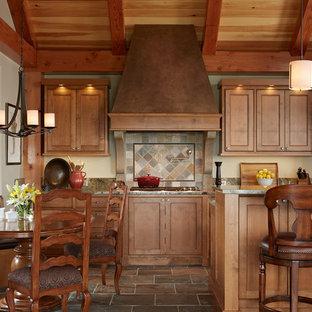 Idée de décoration pour une grand cuisine américaine craftsman en L avec un placard à porte affleurante, un électroménager en acier inoxydable, des portes de placard en bois brun, un évier encastré, un plan de travail en granite, une crédence multicolore, un sol en ardoise, un îlot central, une crédence en ardoise et un sol multicolore.