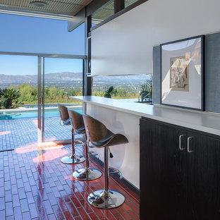 他の地域のミッドセンチュリースタイルのおしゃれなキッチン (セラミックタイルの床、フラットパネル扉のキャビネット、黒いキャビネット、人工大理石カウンター、赤い床、白いキッチンカウンター) の写真