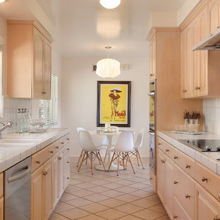 Photo of a small midcentury galley eat-in kitchen in Los Angeles with a double-bowl sink, raised-panel cabinets, light wood cabinets, tile benchtops, white splashback, porcelain splashback, stainless steel appliances, porcelain floors, beige floor and white benchtop.