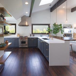 ロサンゼルスの中サイズのエクレクティックスタイルのおしゃれなキッチン (アンダーカウンターシンク、シェーカースタイル扉のキャビネット、青いキャビネット、人工大理石カウンター、白いキッチンパネル、サブウェイタイルのキッチンパネル、シルバーの調理設備の、濃色無垢フローリング、茶色い床、白いキッチンカウンター) の写真