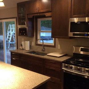 シカゴの中サイズのサンタフェスタイルのおしゃれなキッチン (アンダーカウンターシンク、シェーカースタイル扉のキャビネット、茶色いキャビネット、クオーツストーンカウンター、白いキッチンパネル、サブウェイタイルのキッチンパネル、シルバーの調理設備の) の写真