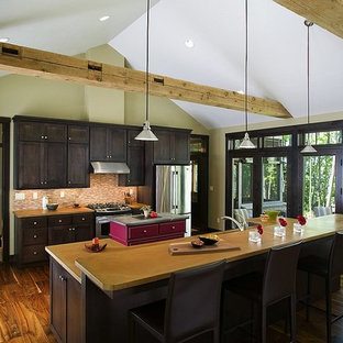 Large rustic eat-in kitchen ideas - Eat-in kitchen - large rustic single-wall medium tone wood floor eat-in kitchen idea in Other with shaker cabinets, dark wood cabinets, solid surface countertops, beige backsplash, matchstick tile backsplash, stainless steel appliances and two islands