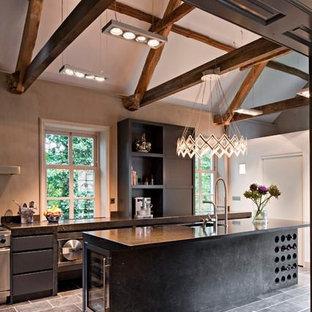 他の地域の広いトランジショナルスタイルのおしゃれなキッチン (アンダーカウンターシンク、フラットパネル扉のキャビネット、黒いキャビネット、オニキスカウンター、シルバーの調理設備、セラミックタイルの床) の写真