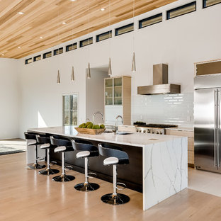 Idéer för ett mycket stort modernt vit linjärt kök med öppen planlösning, med en trippel diskho, luckor med glaspanel, skåp i ljust trä, marmorbänkskiva, vitt stänkskydd, stänkskydd i tunnelbanekakel, rostfria vitvaror och en köksö