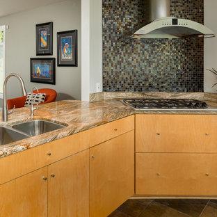 ナッシュビルの広いモダンスタイルのおしゃれなキッチン (ダブルシンク、フラットパネル扉のキャビネット、淡色木目調キャビネット、御影石カウンター、メタリックのキッチンパネル、ガラスタイルのキッチンパネル、シルバーの調理設備、セラミックタイルの床、茶色い床、オレンジのキッチンカウンター) の写真