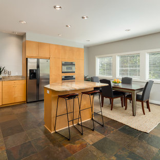 Design ideas for a large modern u-shaped eat-in kitchen in Nashville with a double-bowl sink, flat-panel cabinets, light wood cabinets, granite benchtops, metallic splashback, glass tile splashback, stainless steel appliances, ceramic floors, with island, brown floor and orange benchtop.