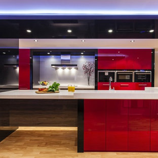 Design ideas for a contemporary single-wall open plan kitchen in Sydney with flat-panel cabinets, red cabinets, glass sheet splashback, plywood flooring and beige floors.