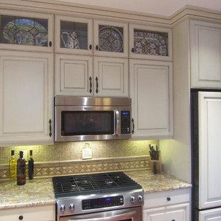 Bild på ett vintage kök, med en undermonterad diskho, vita skåp, granitbänkskiva, beige stänkskydd, integrerade vitvaror och målat trägolv