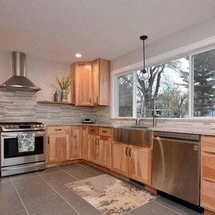 他の地域の大きいおしゃれなキッチン (エプロンフロントシンク、フラットパネル扉のキャビネット、淡色木目調キャビネット、御影石カウンター、マルチカラーのキッチンパネル、ガラスタイルのキッチンパネル、シルバーの調理設備の、セラミックタイルの床、アイランドなし、グレーの床、マルチカラーのキッチンカウンター) の写真