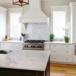 Mid-sized contemporary enclosed kitchen photos - Inspiration for a mid-sized contemporary u-shaped light wood floor and beige floor enclosed kitchen remodel in Charleston with a farmhouse sink, shaker cabinets, white cabinets, quartzite countertops, gray backsplash, matchstick tile backsplash, stainless steel appliances, an island and gray countertops
