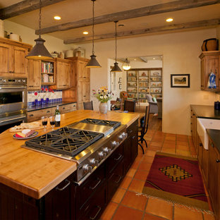 Mid-sized southwestern eat-in kitchen pictures - Inspiration for a mid-sized southwestern u-shaped terra-cotta floor eat-in kitchen remodel in Denver with a farmhouse sink, shaker cabinets, wood countertops, multicolored backsplash, ceramic backsplash, stainless steel appliances, an island and dark wood cabinets