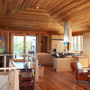 Réalisation d'une très grand cuisine ouverte design en U avec un évier posé, un placard à porte plane, des portes de placard en bois clair, un électroménager encastrable et un îlot central.