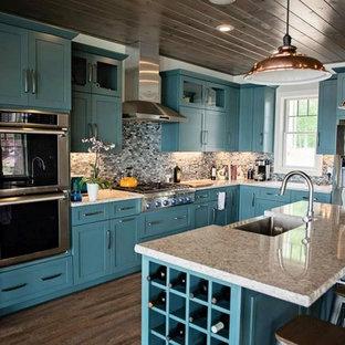 インディアナポリスのシャビーシック調のおしゃれなアイランドキッチン (アンダーカウンターシンク、青いキャビネット、御影石カウンター、マルチカラーのキッチンパネル、ガラスタイルのキッチンパネル、シルバーの調理設備の、クッションフロア) の写真