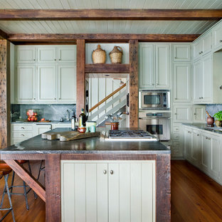 Farmhouse kitchen remodeling - Example of a farmhouse medium tone wood floor and brown floor kitchen design in Atlanta with green cabinets, an undermount sink, recessed-panel cabinets, black backsplash, stainless steel appliances and an island