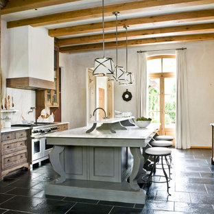 Ispirazione per una cucina parallela mediterranea con ante con riquadro incassato, ante in legno bruno, elettrodomestici da incasso, isola e pavimento nero