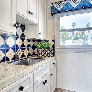 オレンジカウンティの小さい地中海スタイルのおしゃれなキッチン (アンダーカウンターシンク、レイズドパネル扉のキャビネット、白いキャビネット、タイルカウンター、青いキッチンパネル、セラミックタイルのキッチンパネル、シルバーの調理設備の、磁器タイルの床、白いキッチンカウンター) の写真