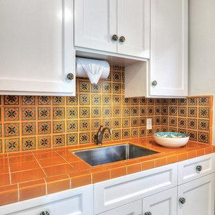 Modelo de cocina mediterránea con fregadero bajoencimera, encimera de azulejos, salpicadero naranja, salpicadero de azulejos de cerámica, electrodomésticos de acero inoxidable y encimeras naranjas