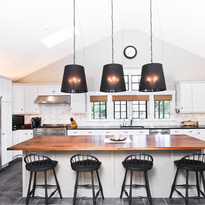 Example of a large transitional u-shaped slate floor and gray floor eat-in kitchen design in Boston with an undermount sink, white cabinets, wood countertops, gray backsplash, stone tile backsplash, stainless steel appliances, an island and shaker cabinets