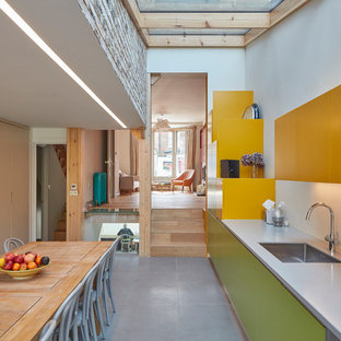 Design ideas for a medium sized contemporary single-wall kitchen/diner in London with a submerged sink, flat-panel cabinets, no island, grey floors and yellow cabinets.