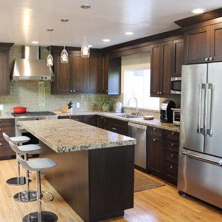 Inspiration för små klassiska kök, med en undermonterad diskho, bruna skåp, bänkskiva i kvarts, grönt stänkskydd, stänkskydd i glaskakel, rostfria vitvaror, ljust trägolv, en köksö och skåp i shakerstil