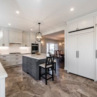 Photo of a large contemporary u-shaped eat-in kitchen in Toronto with an undermount sink, recessed-panel cabinets, white cabinets, quartzite benchtops, ceramic splashback, stainless steel appliances, porcelain floors, with island, brown floor and turquoise benchtop.