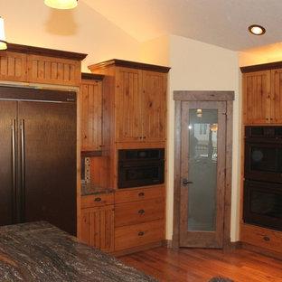 グランドラピッズのラスティックスタイルのおしゃれなキッチン (ダブルシンク、ルーバー扉のキャビネット、中間色木目調キャビネット、御影石カウンター、ベージュキッチンパネル、モザイクタイルのキッチンパネル、黒い調理設備、無垢フローリング) の写真
