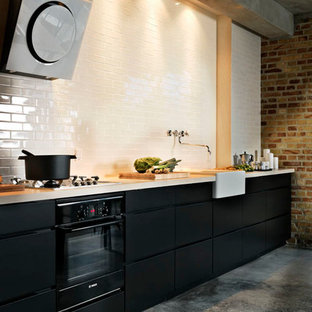 This is an example of a mid-sized industrial single-wall eat-in kitchen in Other with a drop-in sink, louvered cabinets, black cabinets, quartzite benchtops, white splashback, ceramic splashback, white appliances and concrete floors.