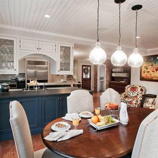 Exemple d'une grande cuisine victorienne en L avec un évier encastré, un placard avec porte à panneau surélevé, des portes de placard en bois sombre, un plan de travail en marbre, une crédence rouge, une crédence en brique, un électroménager en acier inoxydable, un sol en bois brun, un îlot central et un sol marron.