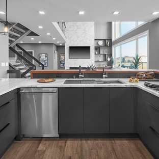 Photo of a large modern l-shaped kitchen/diner in Edmonton with a triple-bowl sink, flat-panel cabinets, grey cabinets, engineered stone countertops, grey splashback, porcelain splashback, stainless steel appliances, medium hardwood flooring, an island, brown floors and white worktops.
