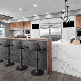 Idéer för att renovera ett stort funkis vit vitt kök, med en trippel diskho, släta luckor, grå skåp, bänkskiva i kvarts, grått stänkskydd, stänkskydd i porslinskakel, rostfria vitvaror, mellanmörkt trägolv, en köksö och brunt golv