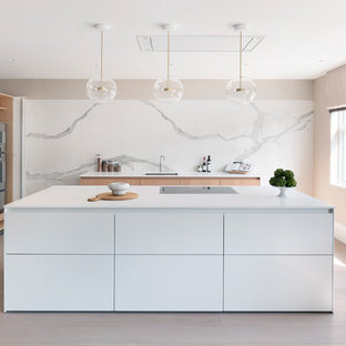 This is an example of a scandinavian kitchen in London with a single-bowl sink, flat-panel cabinets, white cabinets, white splashback, marble splashback, light hardwood flooring, an island, beige floors and white worktops.