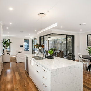 Inspiration for a large contemporary galley kitchen in Sydney with an undermount sink, flat-panel cabinets, white cabinets, medium hardwood floors, with island, brown floor and white benchtop.