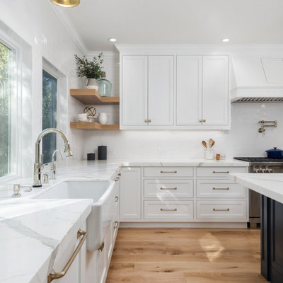 Example of a large country medium tone wood floor and brown floor open concept kitchen design in San Francisco with a farmhouse sink, beaded inset cabinets, white cabinets, marble countertops, white backsplash, ceramic backsplash, paneled appliances, an island and white countertops