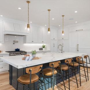 サンフランシスコの大きいカントリー風おしゃれなキッチン (エプロンフロントシンク、インセット扉のキャビネット、白いキャビネット、大理石カウンター、白いキッチンパネル、セラミックタイルのキッチンパネル、パネルと同色の調理設備、無垢フローリング、茶色い床、白いキッチンカウンター) の写真