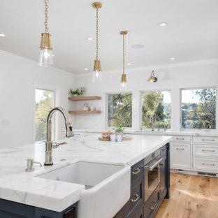 Bild på ett stort lantligt vit vitt kök, med en rustik diskho, vita skåp, marmorbänkskiva, vitt stänkskydd, stänkskydd i keramik, integrerade vitvaror, mellanmörkt trägolv, en köksö, brunt golv och skåp i shakerstil