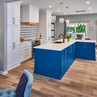 シャーロットの中サイズのエクレクティックスタイルのおしゃれなキッチン (アンダーカウンターシンク、シェーカースタイル扉のキャビネット、青いキャビネット、クオーツストーンカウンター、マルチカラーのキッチンパネル、モザイクタイルのキッチンパネル、シルバーの調理設備、淡色無垢フローリング、茶色い床、白いキッチンカウンター) の写真