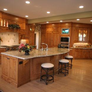 Große Klassische Küche in U-Form mit Vorratsschrank, Doppelwaschbecken, profilierten Schrankfronten, hellbraunen Holzschränken, Speckstein-Arbeitsplatte, Küchenrückwand in Beige, Rückwand aus Travertin, Küchengeräten aus Edelstahl, hellem Holzboden, Kücheninsel und beigem Boden in Cincinnati