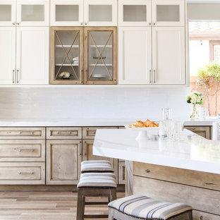 Inspiration för mellanstora klassiska kök, med en rustik diskho, skåp i shakerstil, vita skåp, bänkskiva i kvartsit, vitt stänkskydd, rostfria vitvaror, mellanmörkt trägolv, en halv köksö och brunt golv
